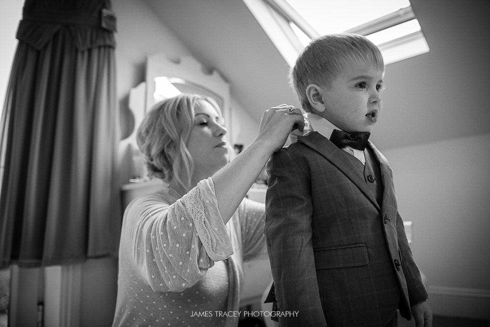 young boy having his wedding suit put on