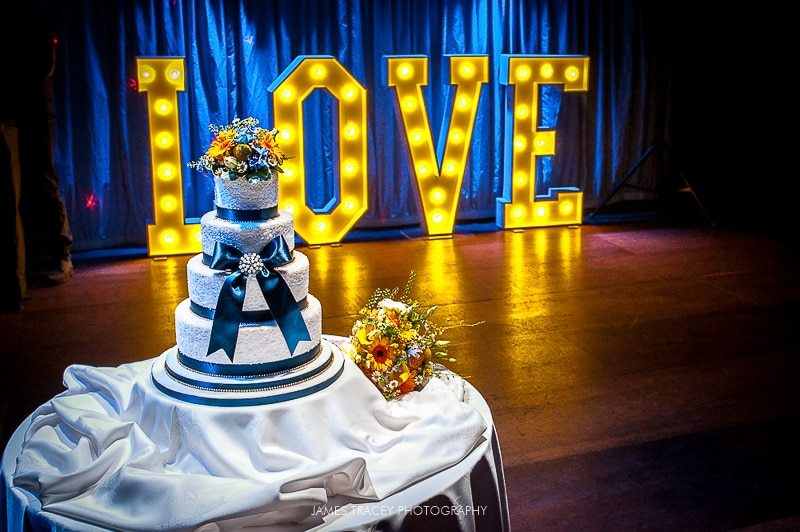 wedding cake in front of light up letters at heaton house farm wedding
