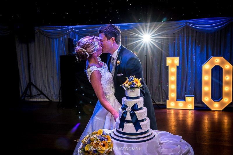 bride and groom kissing after cutting wedding cake at heaton house farm