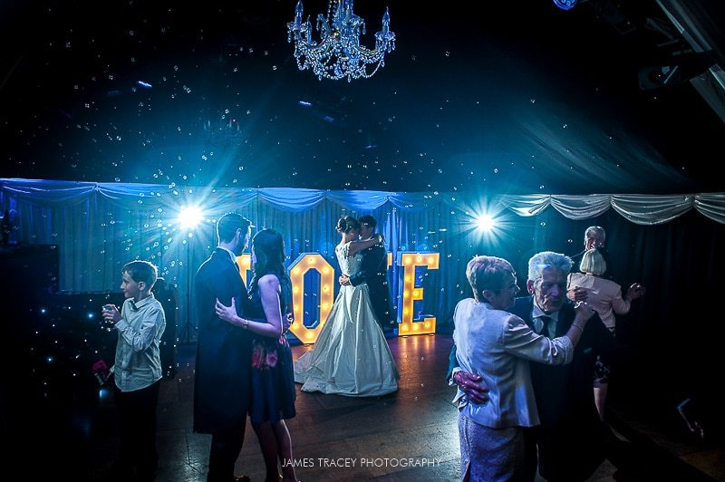 bride and groom first dance in front of light up love letters at heaton house farm