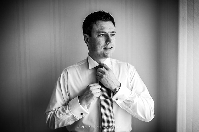 groom putting his wedding tie on before a wedding at Heaton House Farm
