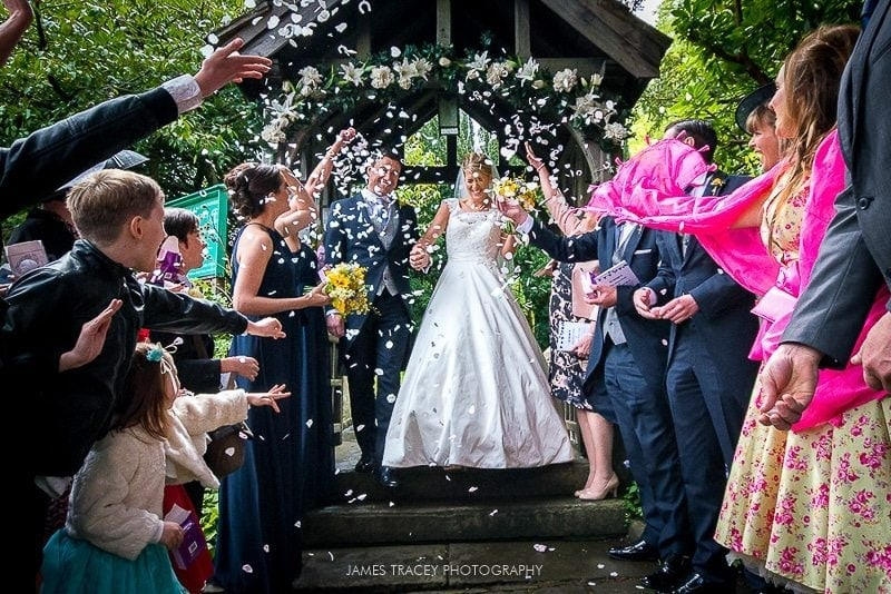 bride and groom having confetti thrown at them at pott shrigley church