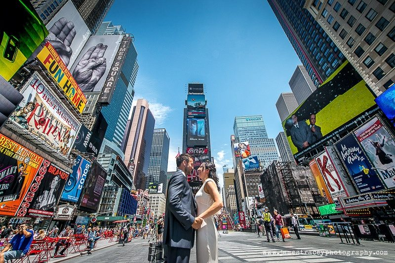 bride and groom kissing in front of times square in new york