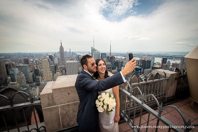 bride and groom taking a selfie on the top of the rock with the empure state building behind them