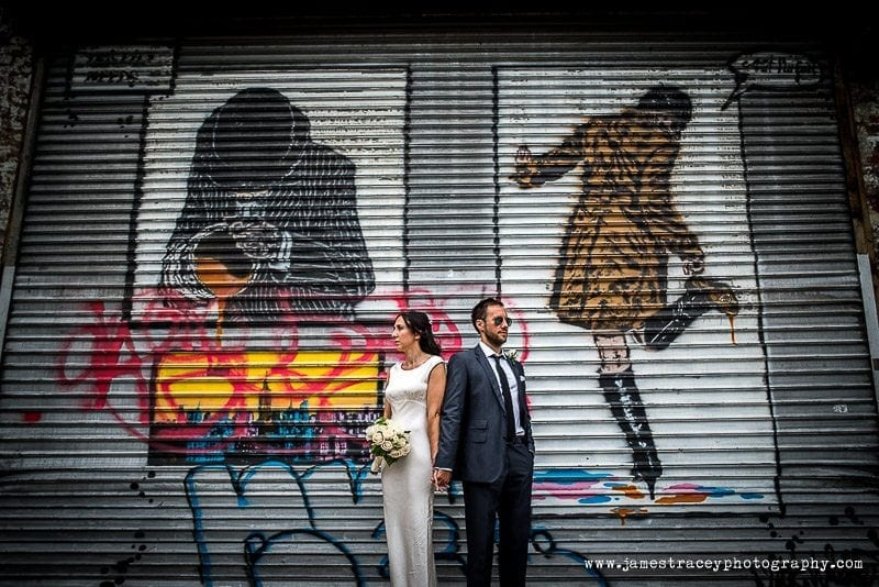bride and groom stood in front of graffiti in the meatpacking district of new york
