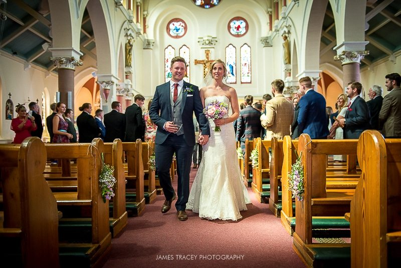 bride and groom walking back down a church aisle