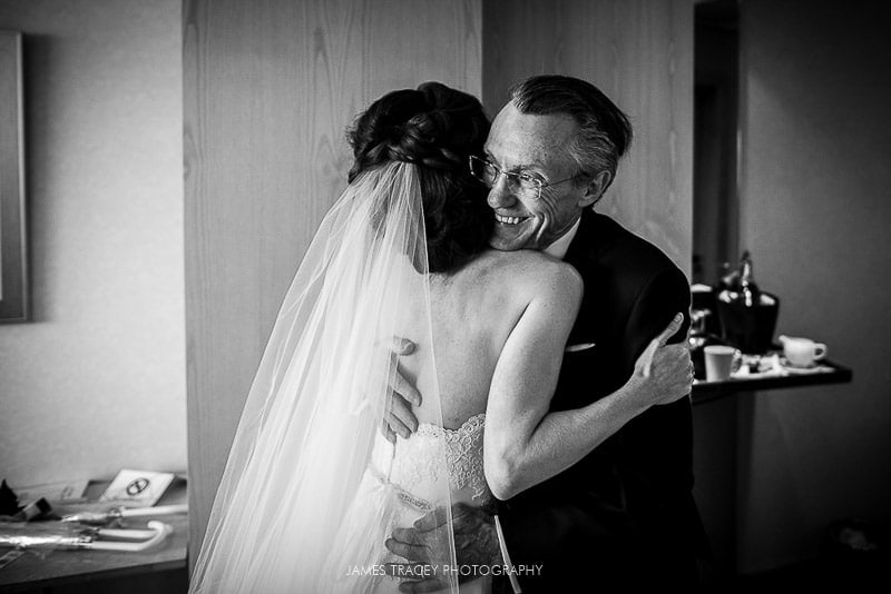 father of the bride hugging his daughter at a wedding
