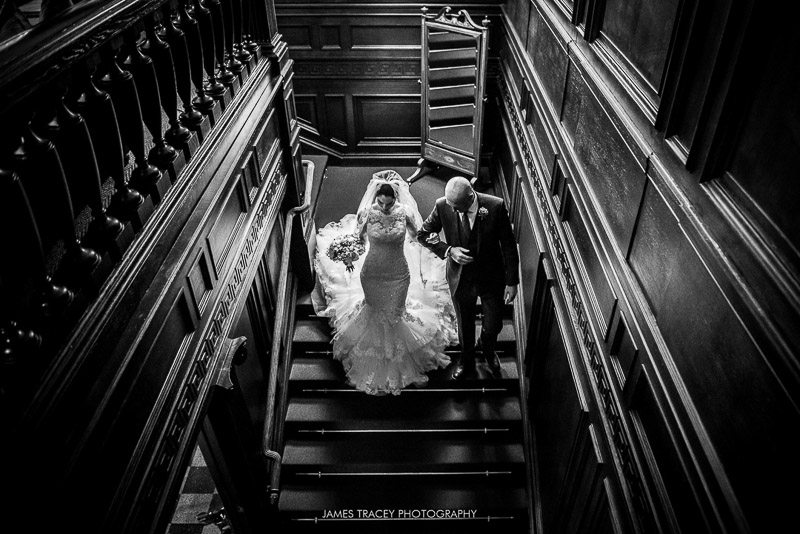 bride walking down stairs at eaves hall in black and white