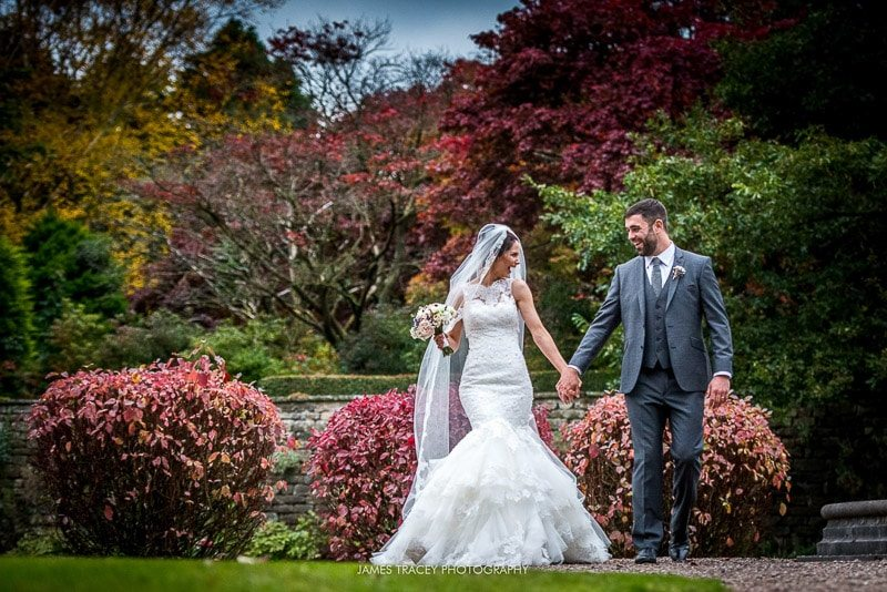 bride and groom walking through eaves hall gardens
