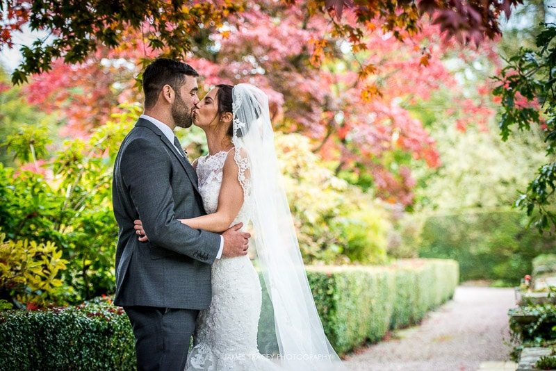 bride and groom kissing under autumnal trees