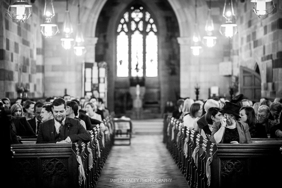 nervous groom at top of church aisle