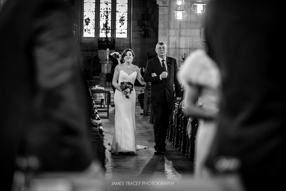 bride and her dad walking up the aisle in black and white
