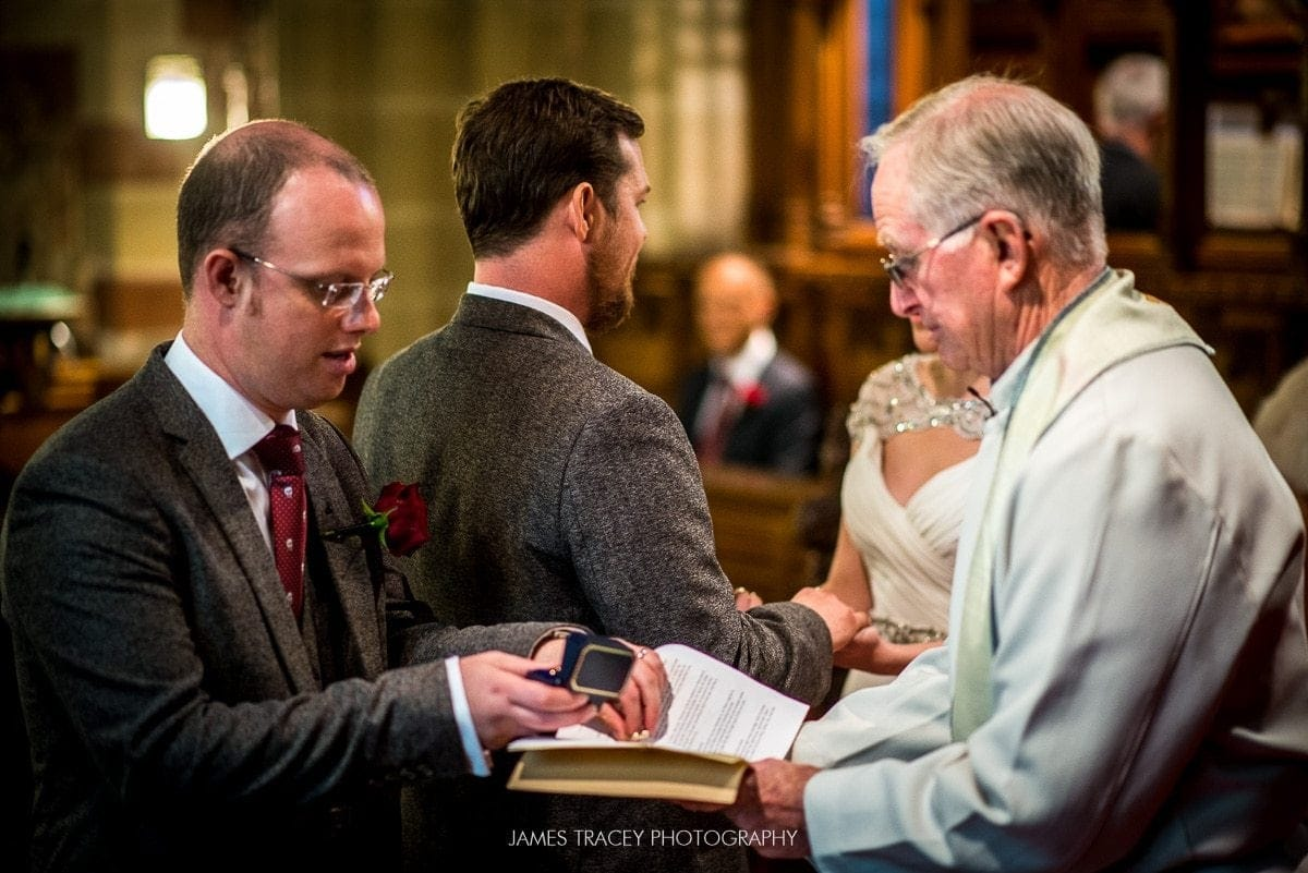 best man passing wedding rings to preist