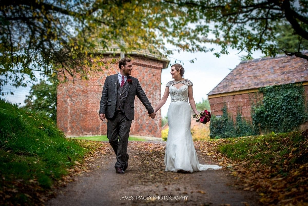 bride and groom walking through autumnal leaves