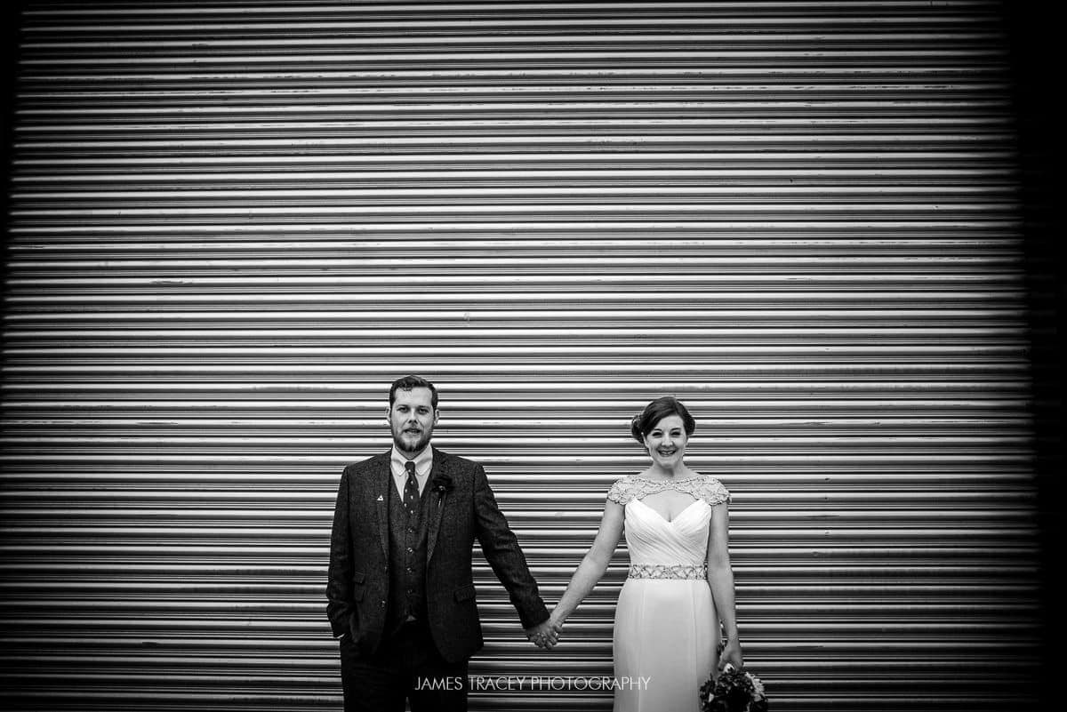bride and groom in front of shutter at a farm