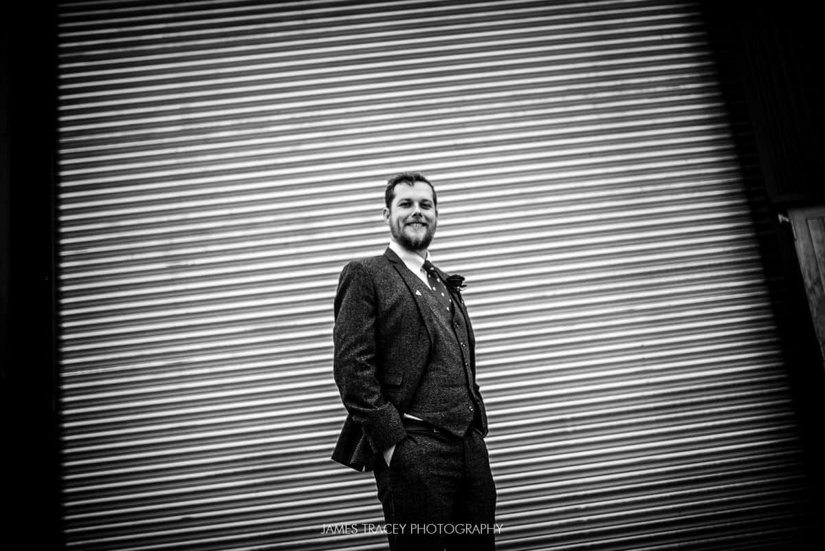 groom posing in front of shutter