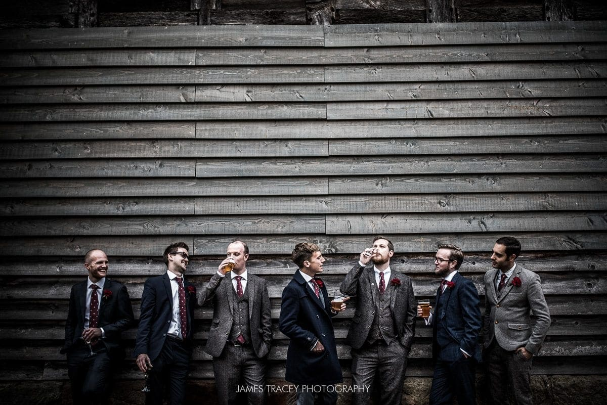 groom and friends drinking in front of wood panelling