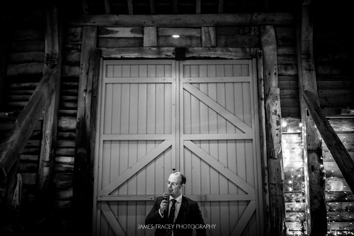 best man speaking in front of large barn door