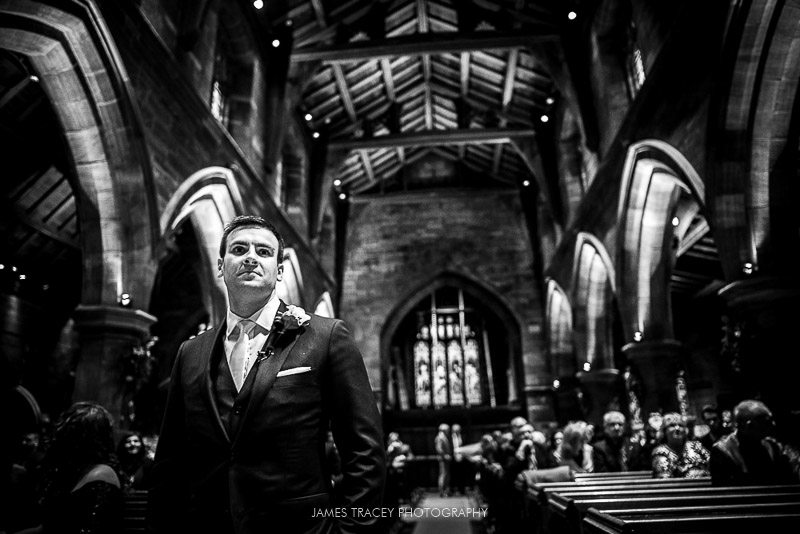 groom wating at top of the wedding aisle
