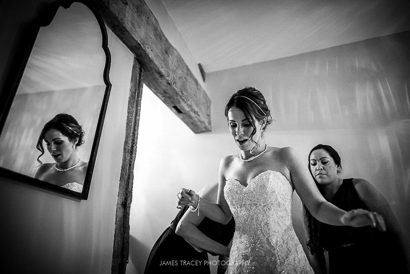 bride getting onto her wedding dress