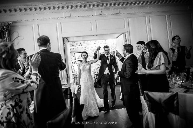 bride and groom walking into reception