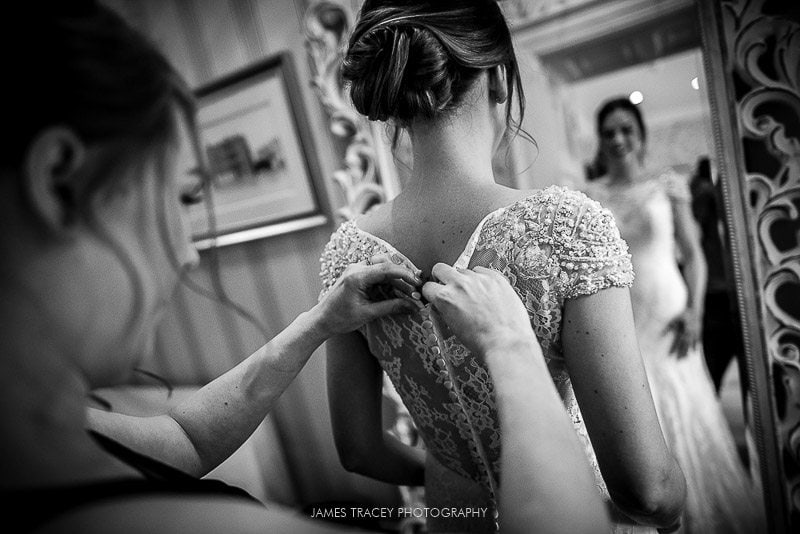 bride being buttoned into wedding dress