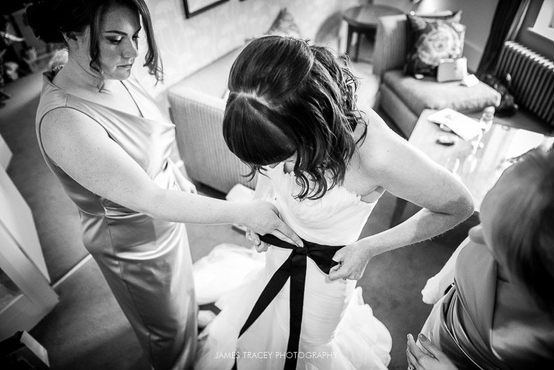 bride being tied into her wedding dress