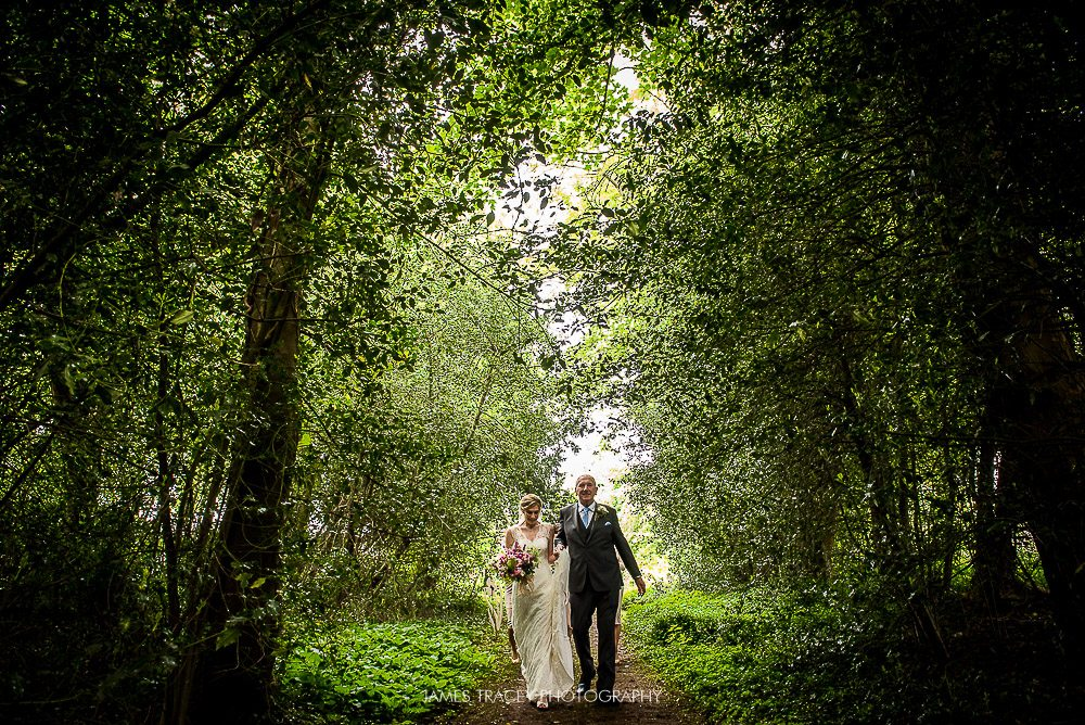 bride walking down aisle under trees