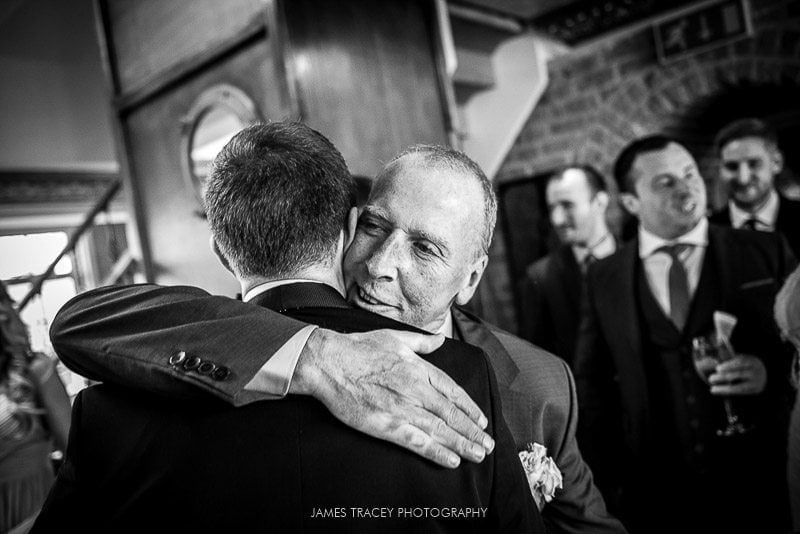 father of the bride hugging groom