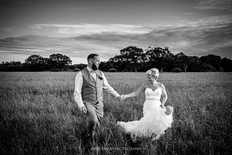 bride and groom walking back through field