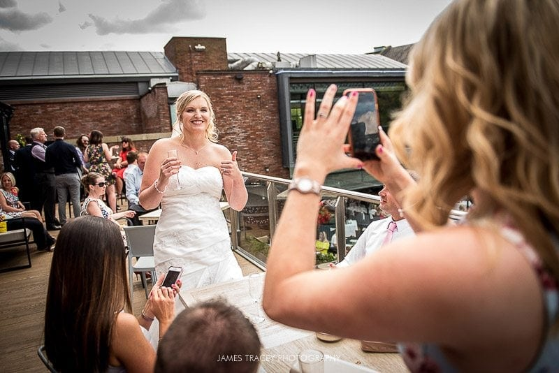 guest taking photo of bride