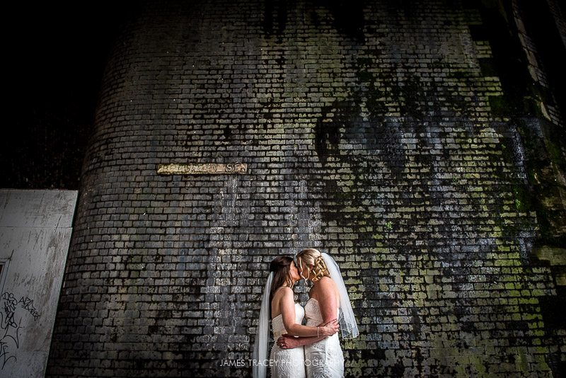 two brides kissing in front of wall