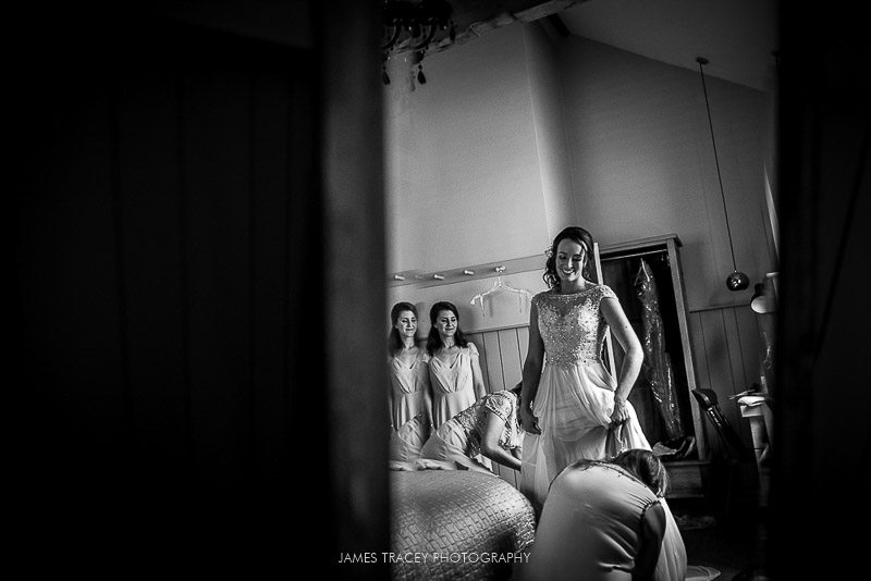 bride putting on her wedding dress