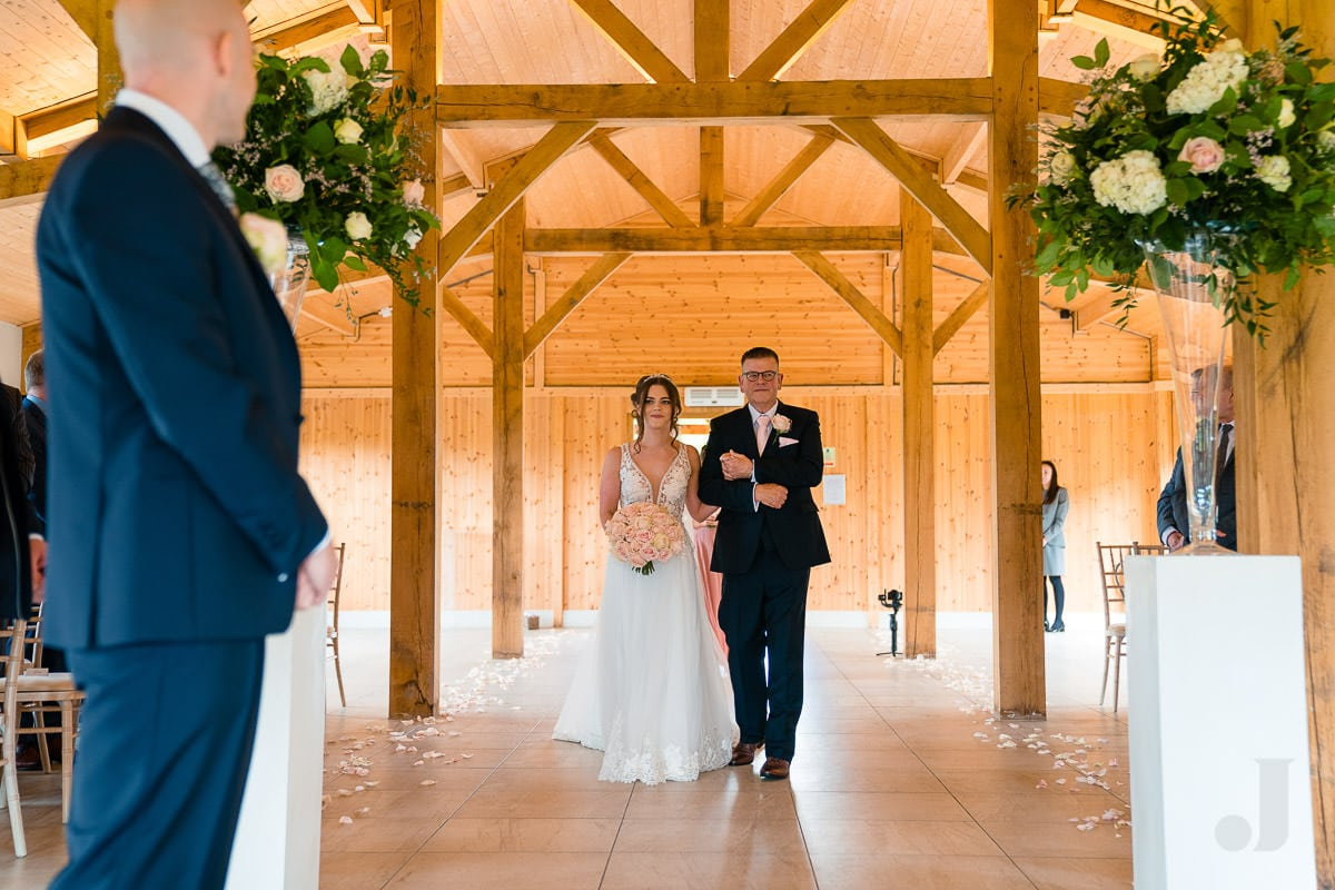 bride walking up the aisle at the stables at merrydale manor