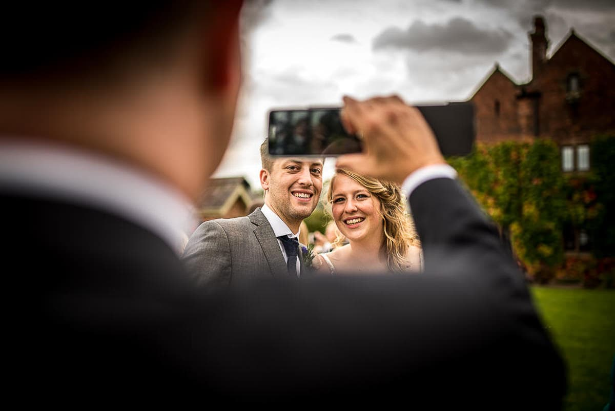 wedding guest taking photos at colshaw hall