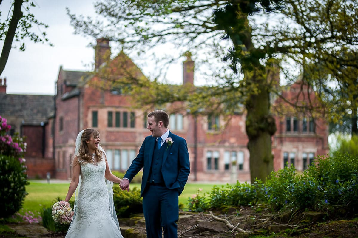 bride and groom with colshaw hall in the background