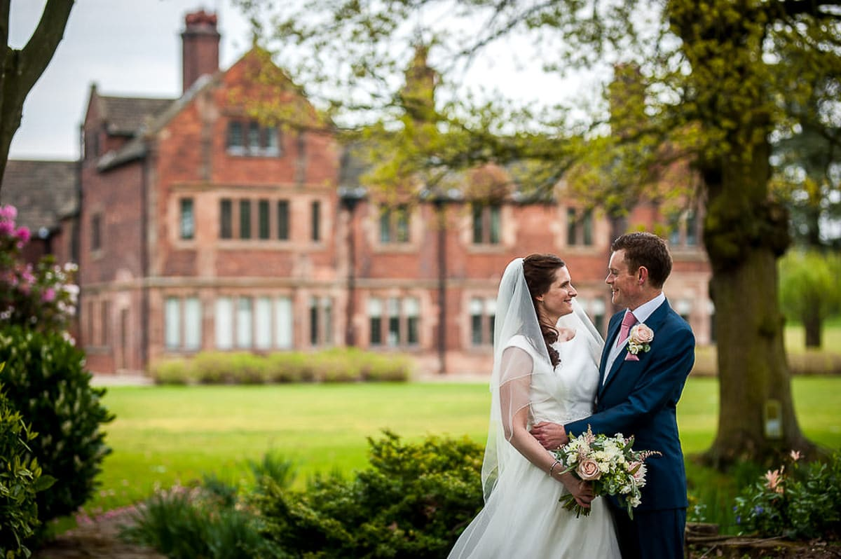 bride and groom posing in front of colshaw hall