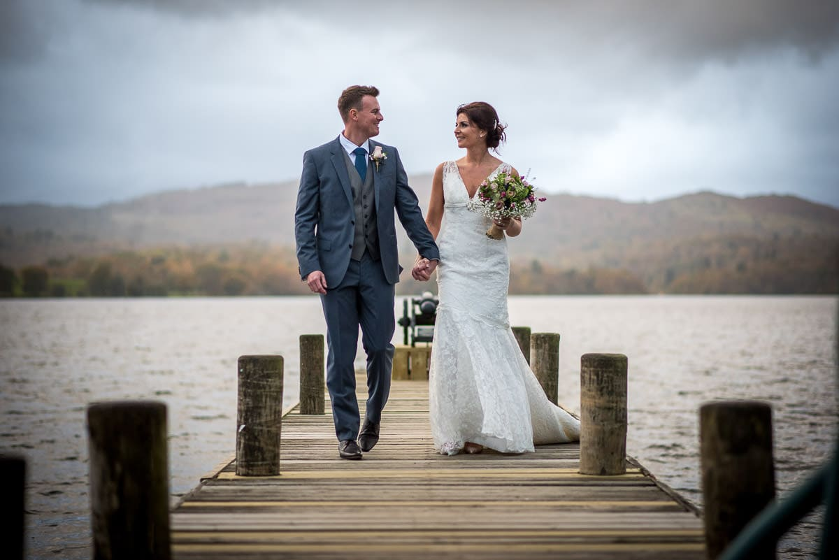 bride and groom walking on lake district jetty