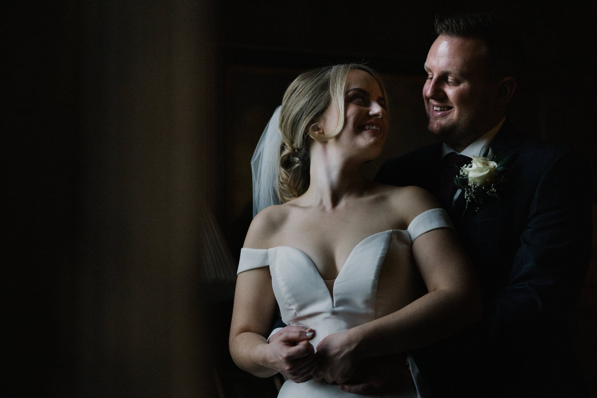 bride and groom in window light at knowsley hall
