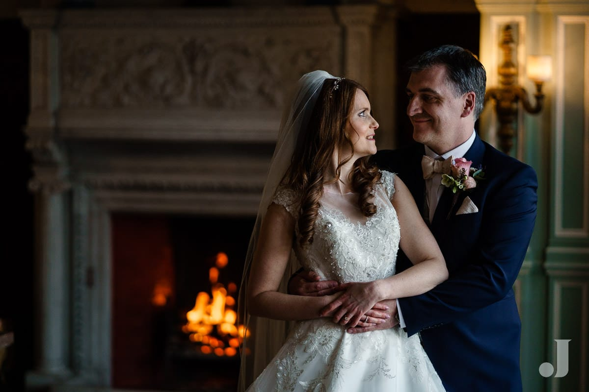 bride and groom in front of open fire at Thornton Manor