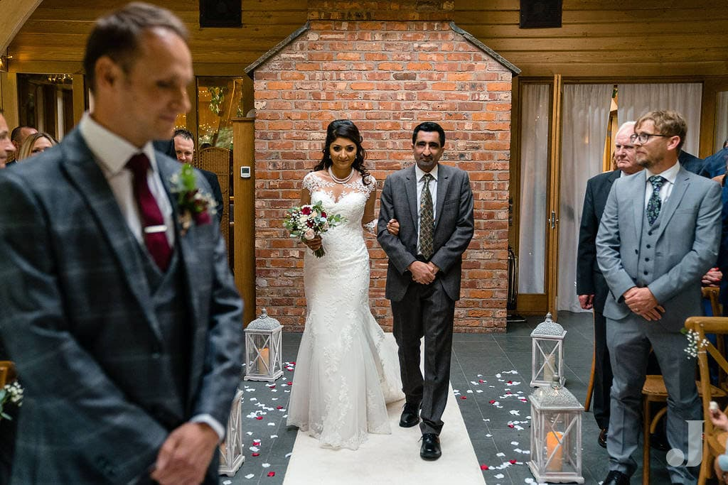 bride walking up the aisle at oak tree of peover