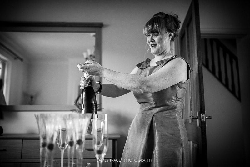 bridesmaid opening a bottle of moet champagne before a wedding at the plough inn in hathersage