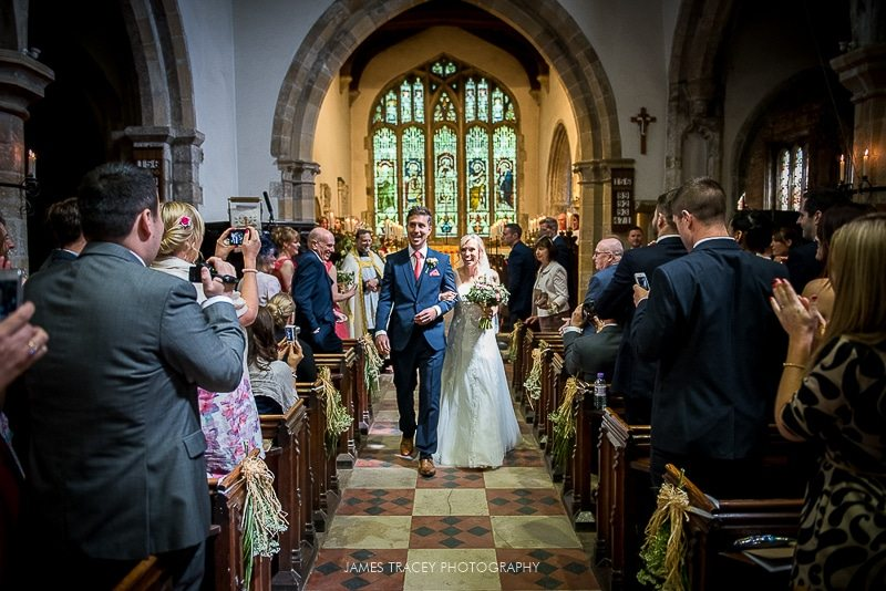 bride and groom walking out of church in hathersage