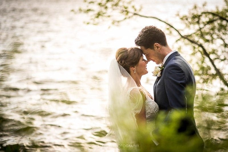 bride and groom sharing a romantic moment in front of lake windermere