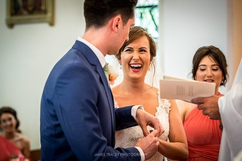 bride laughing as the wedding ring is placed on her finger