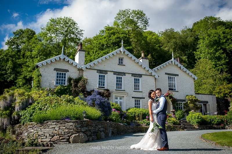 bride and groom stood outside the samling hotel on lake windermere