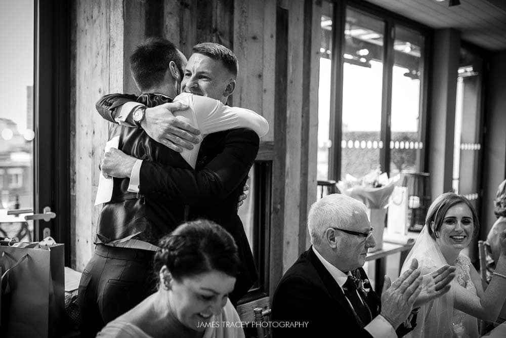 groom hugging best man
