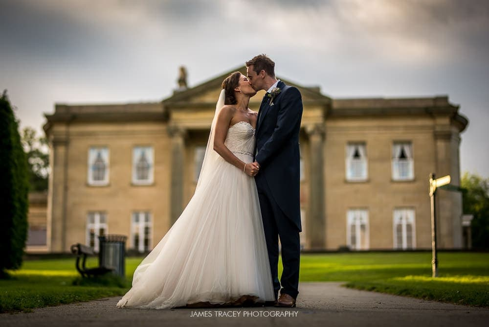 bride and groom kissing in front of the mansion
