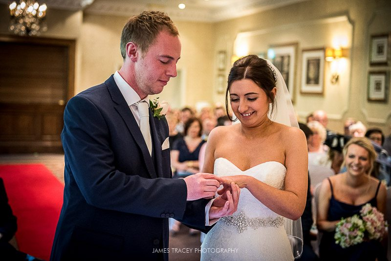 groom putting wedding ring on
