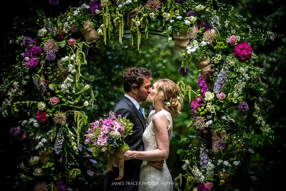 humaist tip garden wedding bride and groom kissing under arch